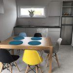 Domki letniskowe Palm Rogowo wnetrze kuchni ze stolem jadalnianym i kompletem krzesel